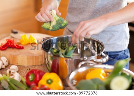 Young woman preparing vegetable soup - stock photo