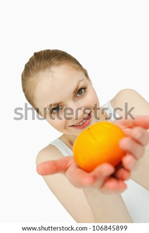 Young woman presenting a tangerine against white background - stock photo