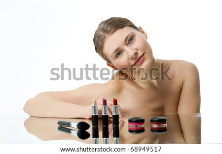 young woman presenting various cosmetic items - stock photo