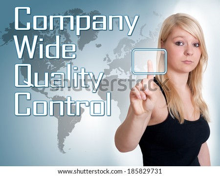Young woman press digital Company Wide Quality Control button on interface in front of her - stock photo