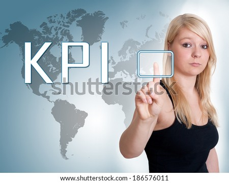 Young woman press digital Key Performance Indicator button on interface in front of her - stock photo