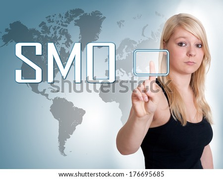 Young woman press digital Social Media Optimization button on interface in front of her - stock photo