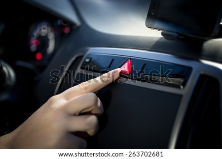 Young woman pressing emergency button on car dashboard