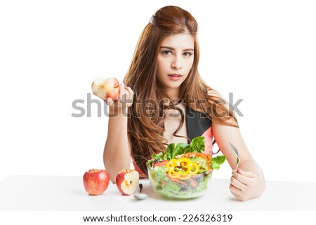 Young woman pretty attractive presenting and eating salad. Portrait of beautiful smiling and happy mixed Asian brunette woman enjoying a healthy salad and cherry tomatoes snack - stock photo