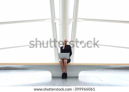 Young woman professional photographer is calling via mobile phone to model which she had found on the network on portable laptop computer to invite her to shooting, while is sitting in modern interior - stock photo