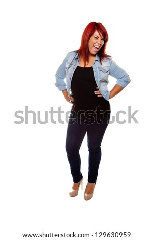 Young woman proudly shows off her physique with her hands on her hips wearing jeans over a white background.