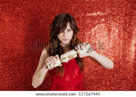 Young woman pulling a Christmas cracker while standing in front of a red glitter background and wearing a red party dress. - stock photo