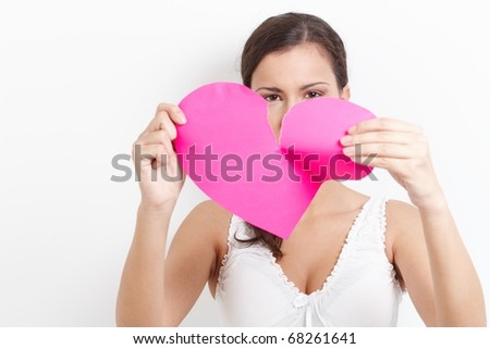 Young woman pulling pink paper heart to pieces.? - stock photo