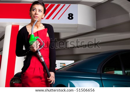 Young woman pumping fuel in her car on gas station - stock photo