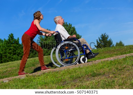 young woman push the old man on wheelchair to the top of the hill in the park