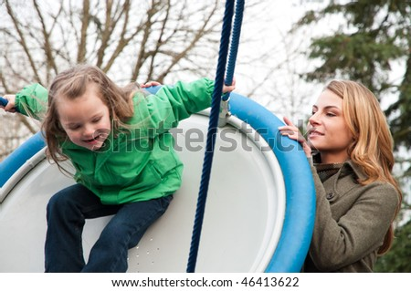 Young woman pushing her daughter on a flying saucer swing at the park, daughter in slight motion blur - stock photo