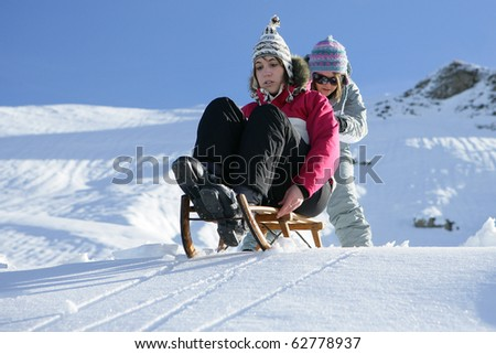 Young woman pushing her friend sitting on a sled in snow - stock photo