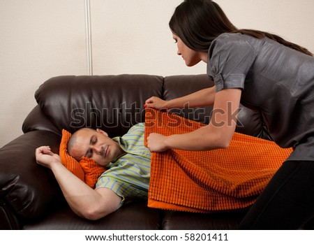 Young woman putting a blanket on her exhausted husband asleep on the sofa - stock photo