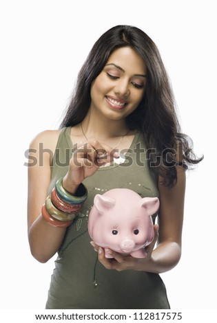 Young woman putting a coin into a piggy bank - stock photo