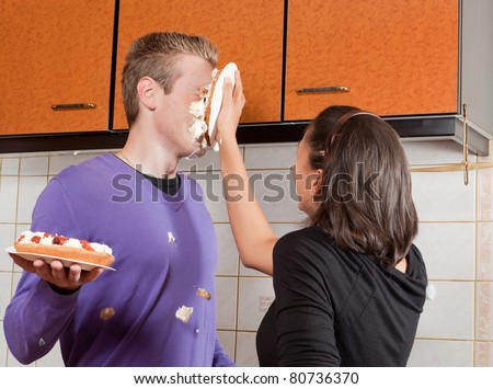 Young woman putting a cream pie in her boyfriend's face - stock photo