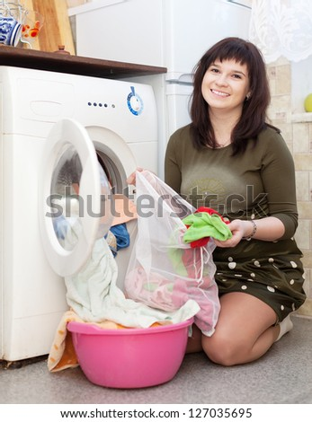 Young woman putting clothes with laundry bag in to washing machine and smiling