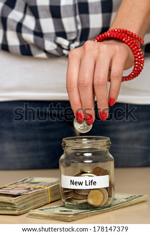 Young woman putting coin into a jar. She is saving money to start a new life. - stock photo