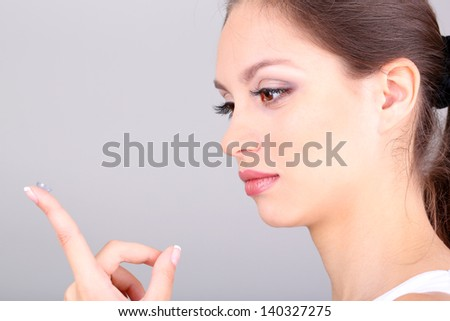 Young woman putting contact lens in her eye on grey background - stock photo