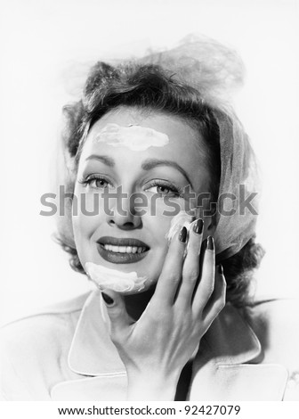 Young woman putting cream onto her face