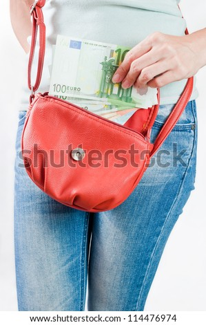 Young woman putting Euro banknotes in a handbag