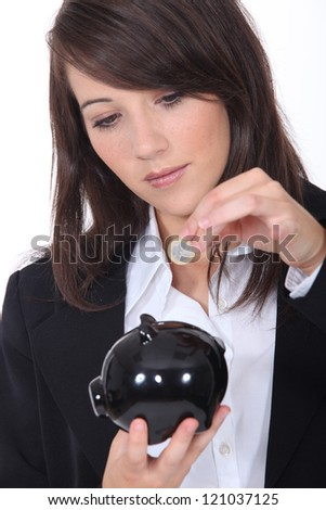 Young woman putting euros into a piggy bank