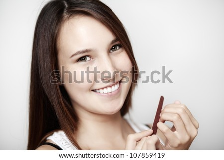 young woman putting filing her nails with a emery board - stock photo