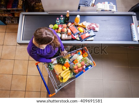Young woman putting goods from shopping cart on counter for checkout in supermarket