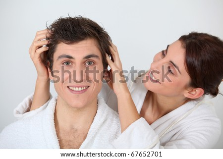 Young woman putting her hands in her boyfriend's hair