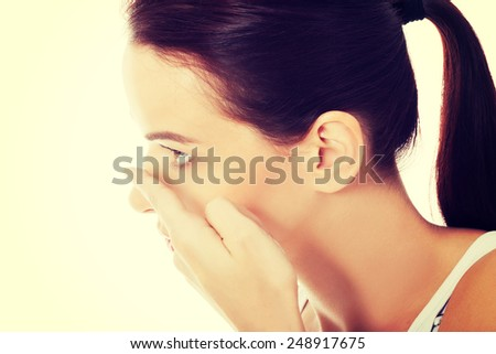 Young woman putting lens into eye. - stock photo