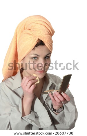 young woman putting make up on her face. Isolated - stock photo