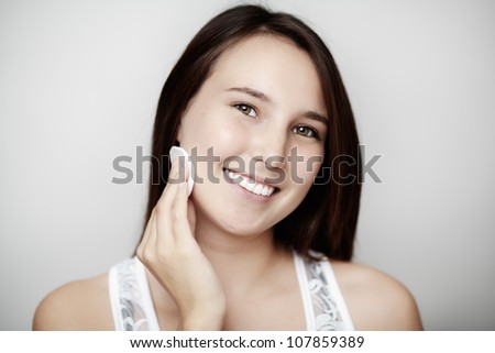 young woman putting make up on with a big smile on her face - stock photo
