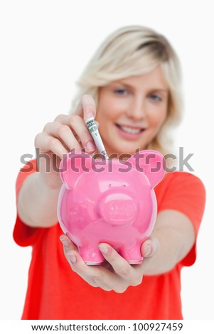 Young woman putting notes into a pink piggy bank against a white background - stock photo