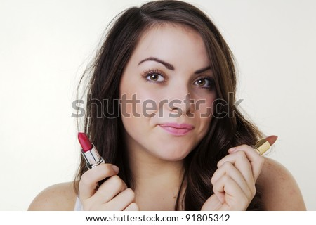 young woman putting on make up shot in the studio - stock photo
