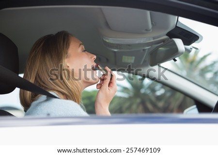 Young woman putting on makeup in her car - stock photo