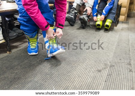 Young Woman putting on shoes for snowboarding. - stock photo