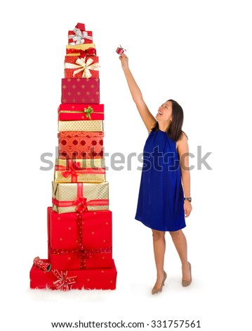 Young woman putting one little gift on top of a huge stack of christmas presents - stock photo