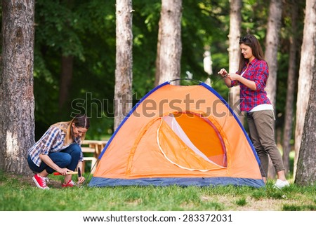 Young woman putting up a tent with her friend??s assistance - stock photo