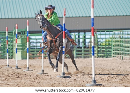 Young woman racing her horse in a rodeo pole bending event. - stock photo