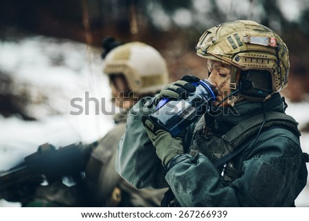 young woman ranger member drink water in forest