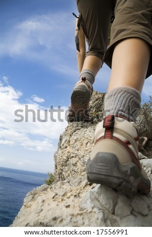 young woman reaching the top of a mountain. - stock photo