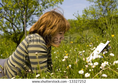 Young woman read a book on meadow field . - stock photo