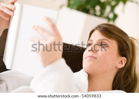 Young woman read book lying down on sofa relaxing in lounge wearing bathrobe