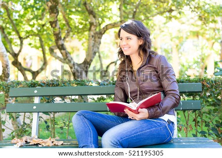 Young woman reading a book and relaxing at the park