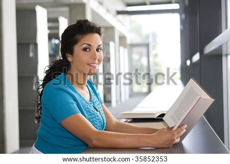 Young woman reading a book at school - stock photo