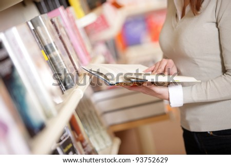 young woman reading a book  in a library, hands close up - stock photo