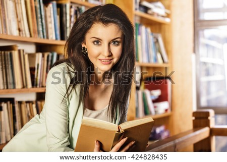 Young woman reading a book in front of bookshelves. Education concept