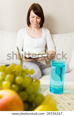 Young woman reading a book in her living room - stock photo