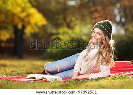 Young woman reading a book in the city park - stock photo