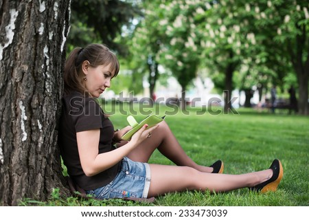 Young woman reading a book in the city park Skopje - stock photo