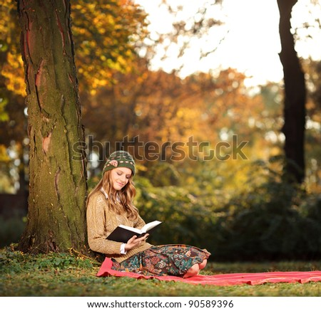 Young woman reading a book in the city park Skopje, Macedonia - stock photo